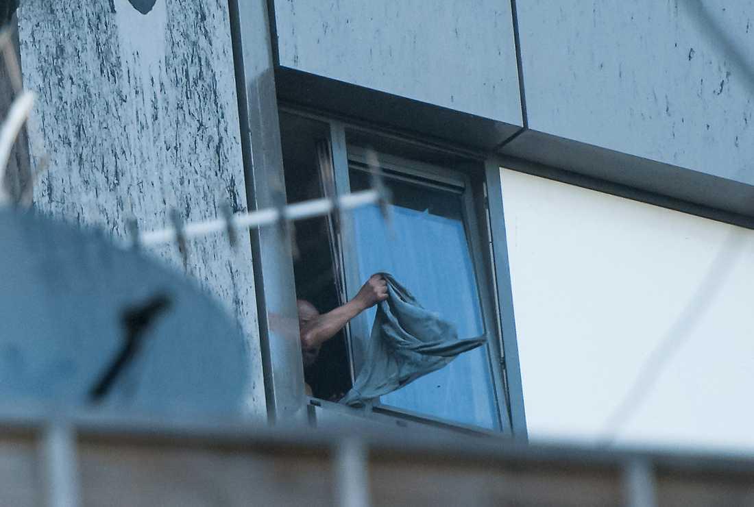 En man vinkar desperat från sin lägenhet i Grenfell Tower. Under honom rasar branden okontrollerat.