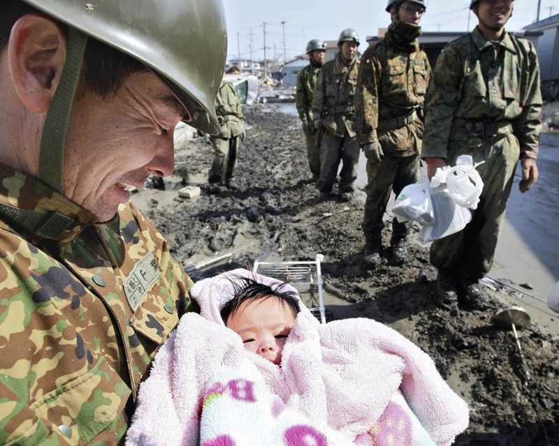 Ljus i mörkret En leende soldat håller en fyramånaders bebis som räddats i Ishinomaki.