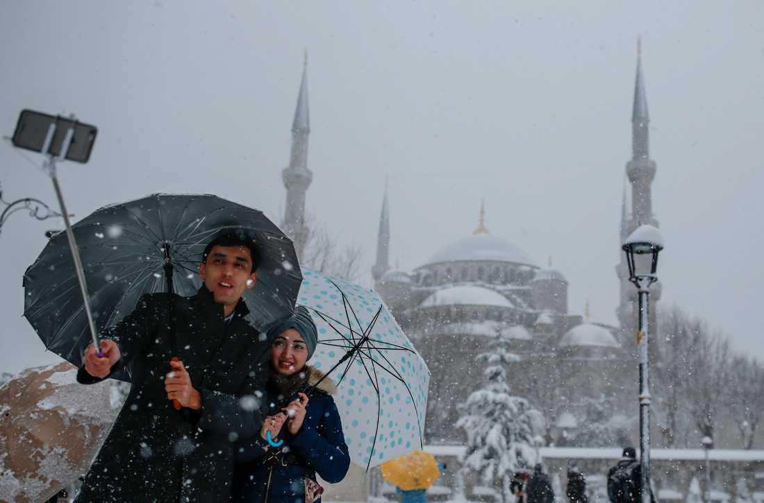 Ett par fotograferar sig framför den Blå moskén i Istanbul.