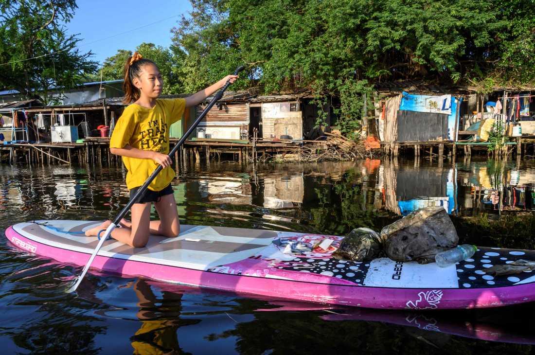 Tolvåriga Ralyn Satidtanasarn paddlar i Bangkok för att fiska upp skräp.