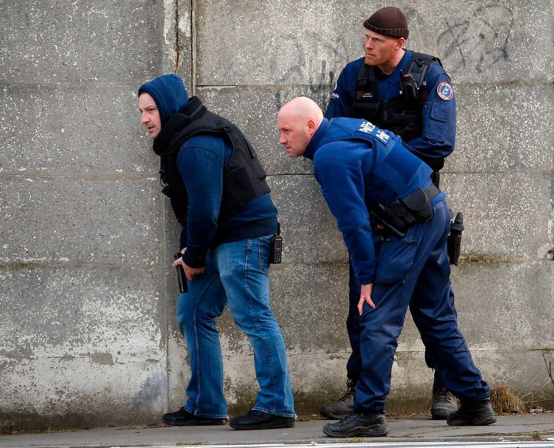 Poliser tar skydd i närheten av platsen där skottlossning bröt ut när polisen gjorde ett tillslag i förorten Forest nära Bryssel.