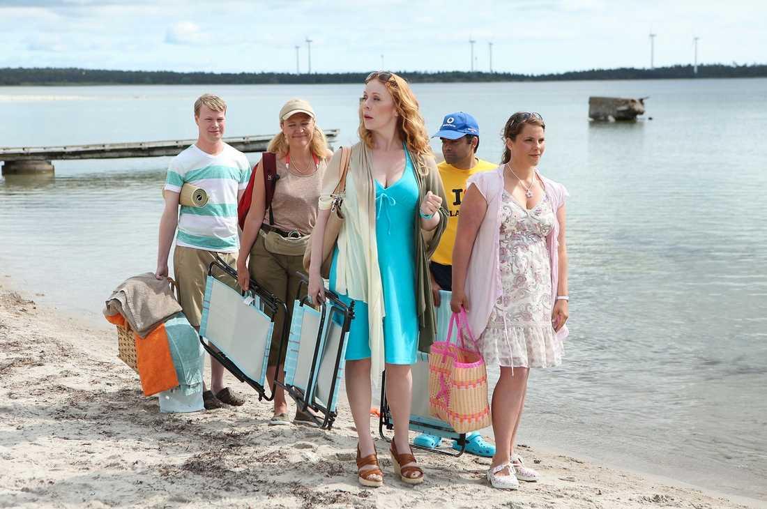 """Ankomsten Här anländer Johan Glans, Klara Zimmergren, Rachel Mohlin, David Batra och Vanna Rosenberg till stranden i en av filmens första scener – som spelas in sista dagen. – Tur att man inte har vräkt i sig en massa kakor under inspelningen, det skulle kunna se konstigt ut. Man får vara vaksam på det där, säger Klara Zimmergren – ett av två nytillskott i """"Skatan""""-gänget. Det är komikerns långfilmsdebut – och hon har definitivt fått mersmak. – Ja men det måste man ju säga. Det är väldigt spännande med alla de här människorna som ingår i ett projekt, det finns folk till allt. Man behöver bara stå där så kommer någon med en varm jacka och smörjer in benen åt en. Jag börjar tänka lite nu, hur ska jag klara av att gå på toa själv?"""