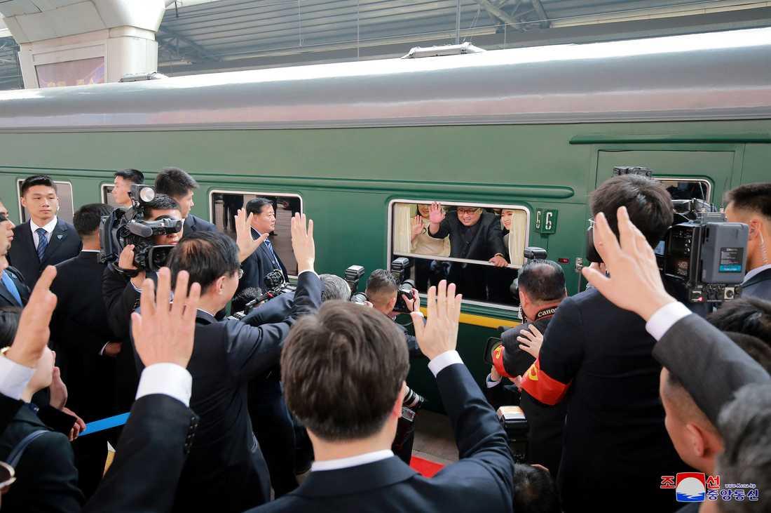 Kim Jong-un vinkar från tåget på tågstationen i Beijing.