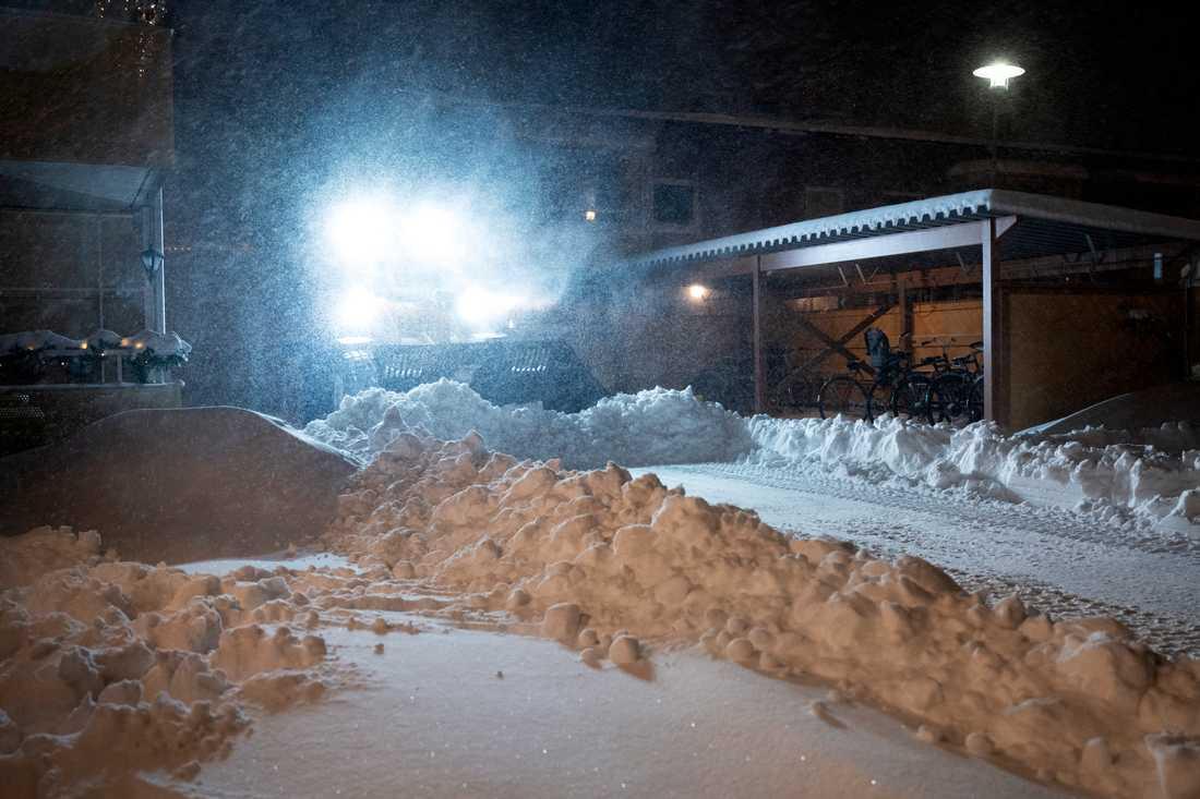 En traktor plogar bland några hus i snöovädret i Umeå, på tisdagsmorgonen den 12 januari.
