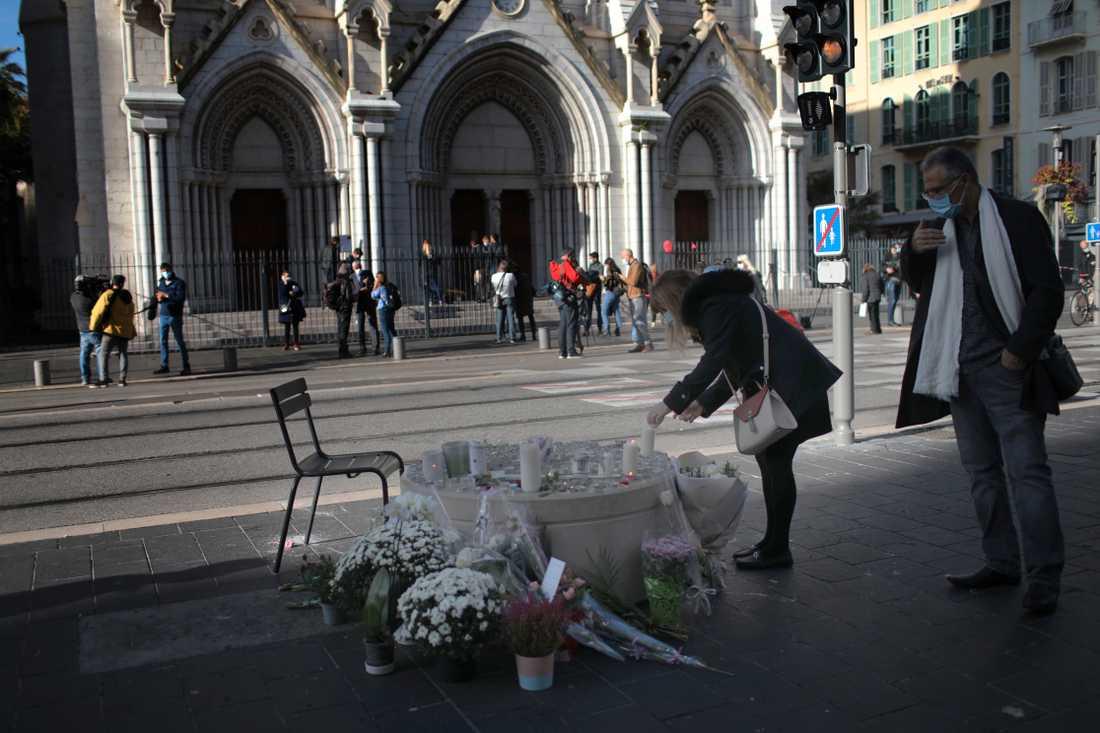 En kvinna tänder ett ljus utanför Notre Dame i Nice, dagen efter knivdådet som tog tre människors liv.