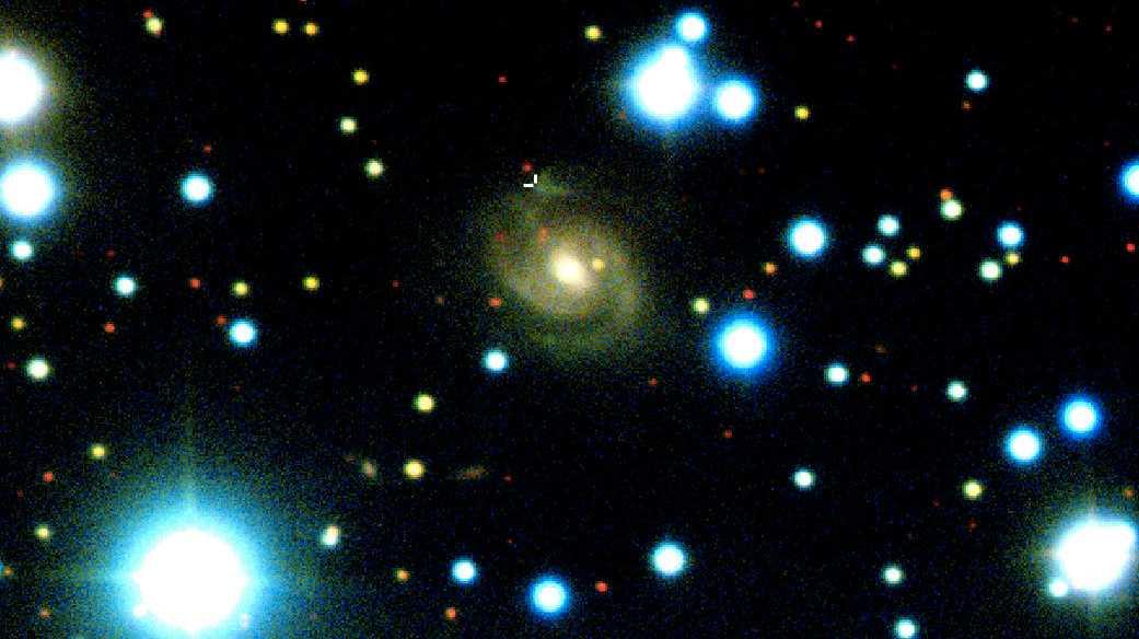 """Till forskarnas förvåning kunde de pulserande radioblixtarna spåras till en """"vanlig"""" spiralgalax på 485 miljoner ljusårs avstånd från jorden. På bilden syns den aktuella galaxen som en gulaktig spiral i bildens mitt. De två vita strecken i dess överkant markerar radiopulsernas ursprung. De andra, ljusstarka blafforna i bilden, är överexponerade stjärnor som ligger långt närmare oss än den aktuella galaxen som ligger bakom en av de stjärntätare delarna av Vintergatan."""