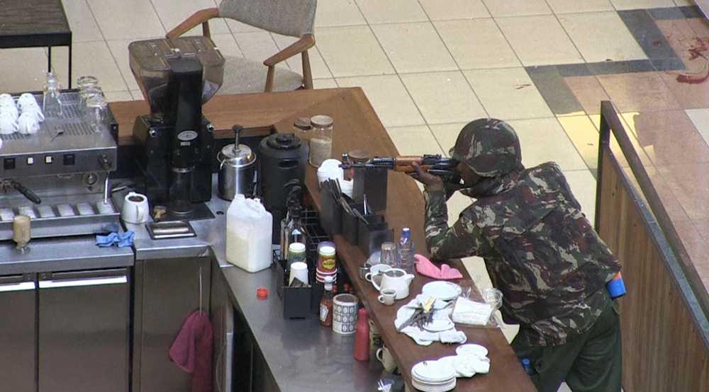 En soldat med kalashnikov smyger vid en kafédisk.