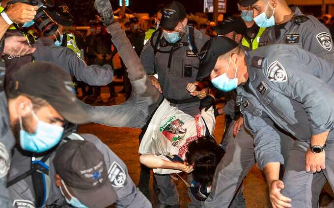 Polis lyfter undan en demonstrant utanför premiärminister Benjamin Netanyahus bostad i Jerusalem på söndagen. Demonstranterna uppmanar Netanyahu att avgå till följd av korruptionsanklagelser.