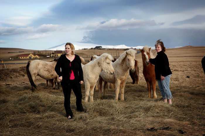 Vigdis H. Olafsdottir och Agnes Charlotte Kruger tar hand om sina hästar. I omgivningarna ligger högvis med svart aska.