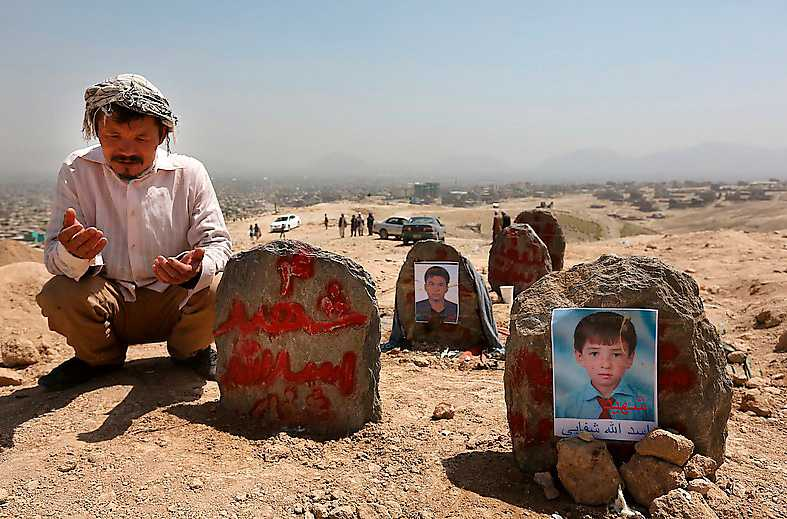 En man ber efter en begravning av offer för en självmordsattack.