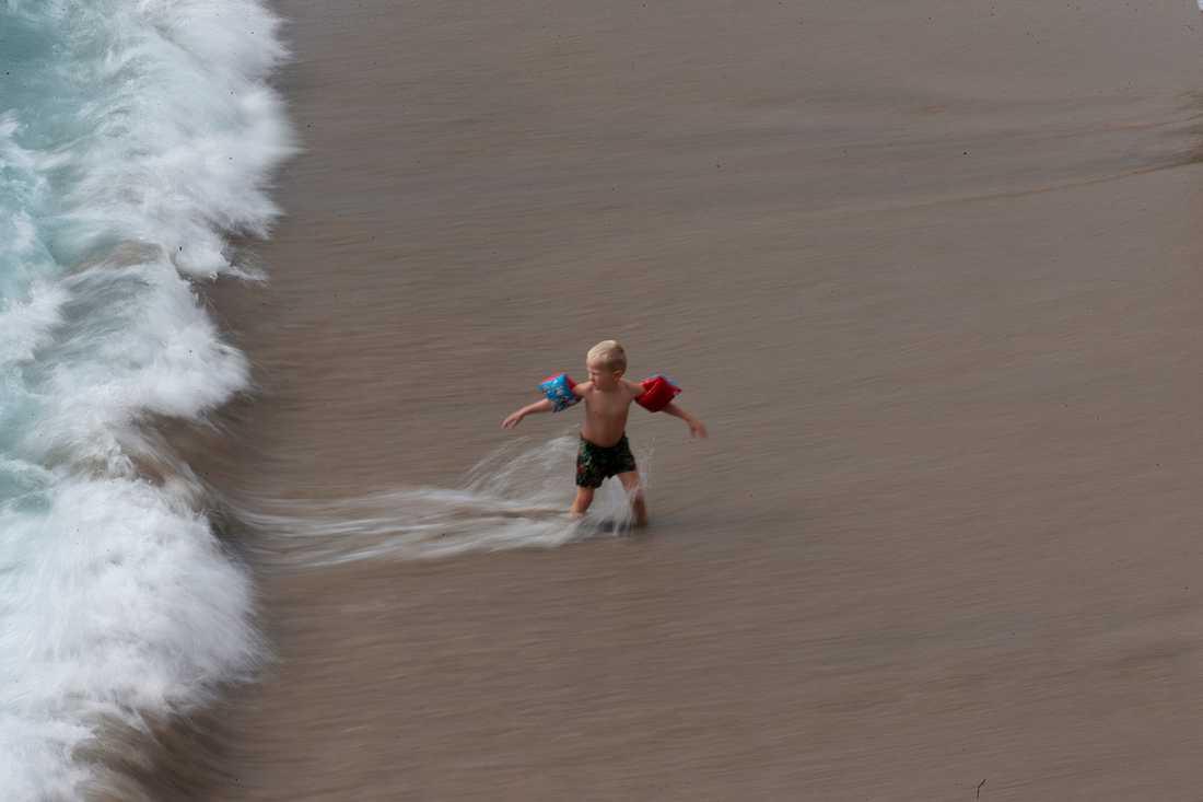 Ett barn leker i vågorna på en strand i Spanien – dock inte i Zahara de los Atunes. Arkivbild.