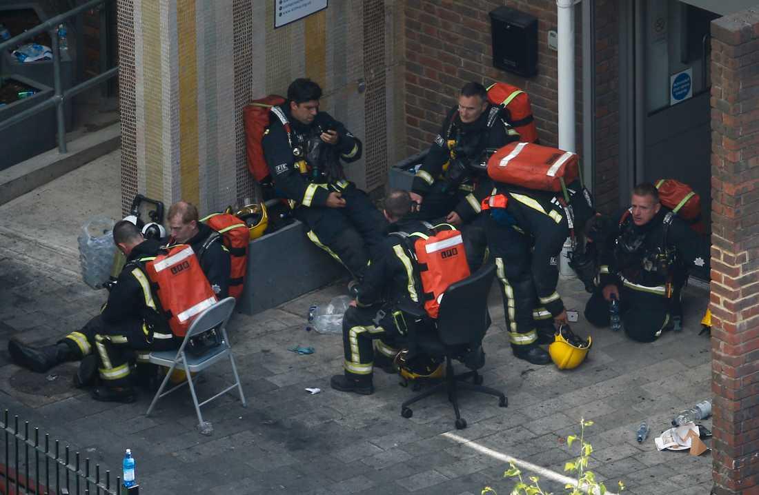 Utmattade brandmän tar en paus efter oändliga timmars kamp mot branden.