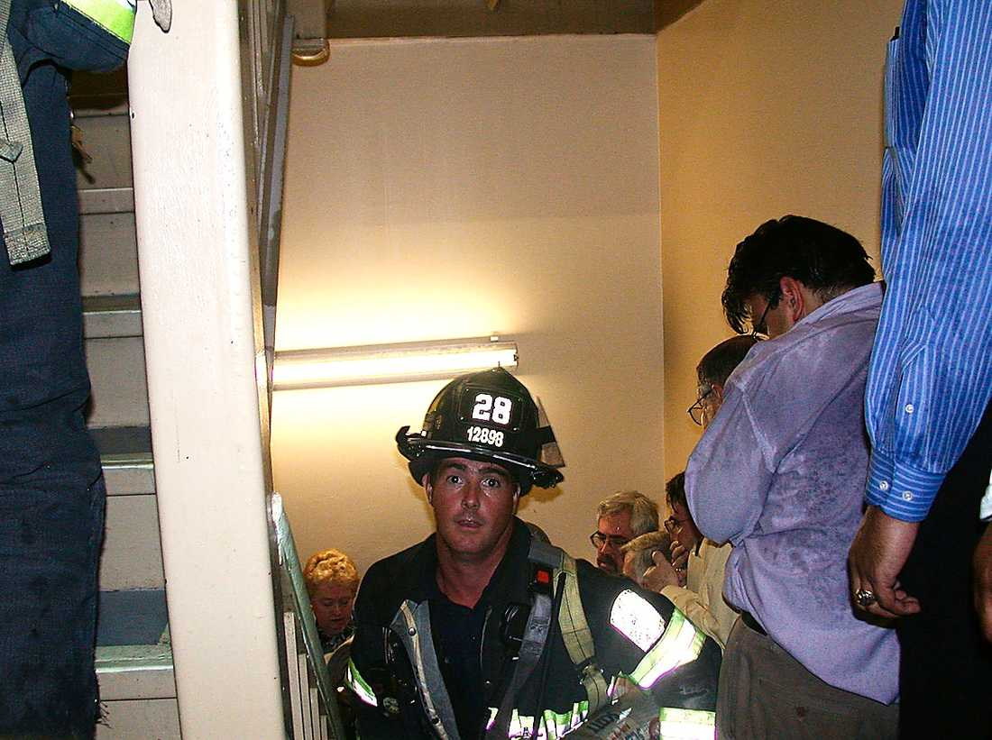 En brandman på väg upp i World Trade Center medan kontorsarbetarna försöker ta sig ut.