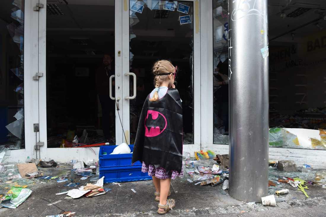 En flicka i batmandräkt står utanför ett plundrat apotek i Schanzenviertel-distriktet i Hamburg.