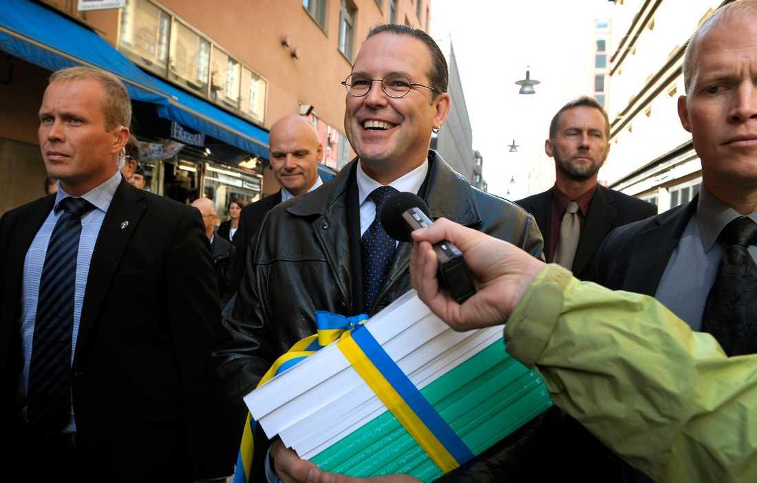 SNACKSALIG Finansminister Anders Borg (M) på väg mot riksdagen med höstbudgeten i en blågul rosett.