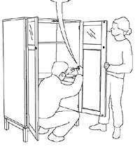 Kvinnan hjälper till när mannen skruvar fast dörren.