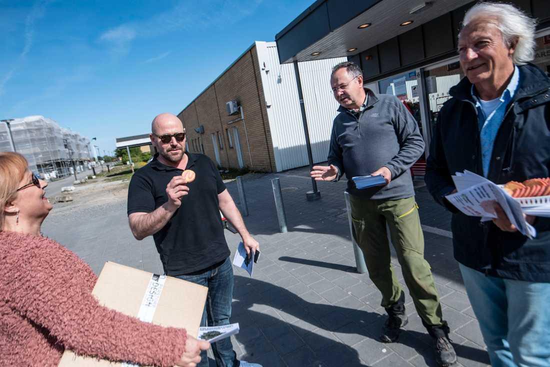 """Therese Jacobsen Ljung stannar till och Dennis Sandström tar en """"nejkaka"""" då ordföranden i partiet Älska Svedala, Mats Bentmar (2:a fr h), delar ut material och Bertil Lindberg (t h), föreningen Fängelsefritt Svedala, bjuder på """"nejkakor"""" utanför Bara centrum i Svedala kommun."""