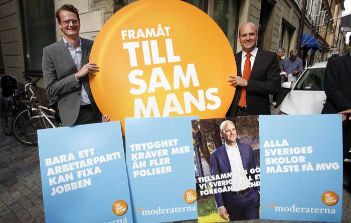 Per Schlingmann och Fredrik Reinfeldt med affischerna som ska vinna valet åt regeringen.