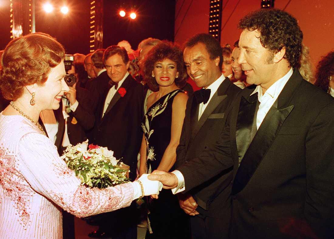 Kenny Lynch tillsammans med sångaren Tom Jones och sångerskan Shirley Bassey när de skakar hand med drottningen Elisabeth den andra.