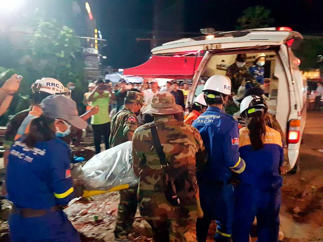 Räddningsarbetare lyfter in ett av offren i en ambulans.