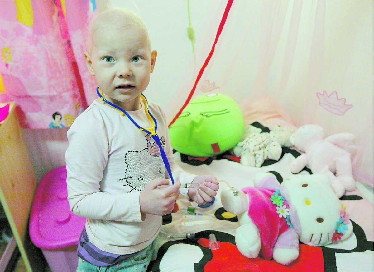 """DOCKAN HAR KANYL Evelina visar gosedockan Kitty som har en kanyl i foten. """"Med en sån slang kan man bli frisk"""", säger hon. När hon blev sjuk trodde man att det var lunginflammation. Sedan kom chocken: leukemi. Nu har man hittat en donator som kan göra Evelina frisk."""