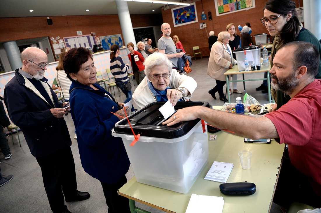 En kvinna lägger sin valsedel i en vallokal i Barcelona.