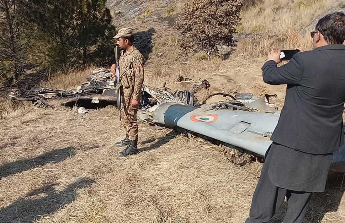 En pakistansk soldat står bredvid det indiska flygplan som sköts ned av pakistansk militär. Arkivbild.