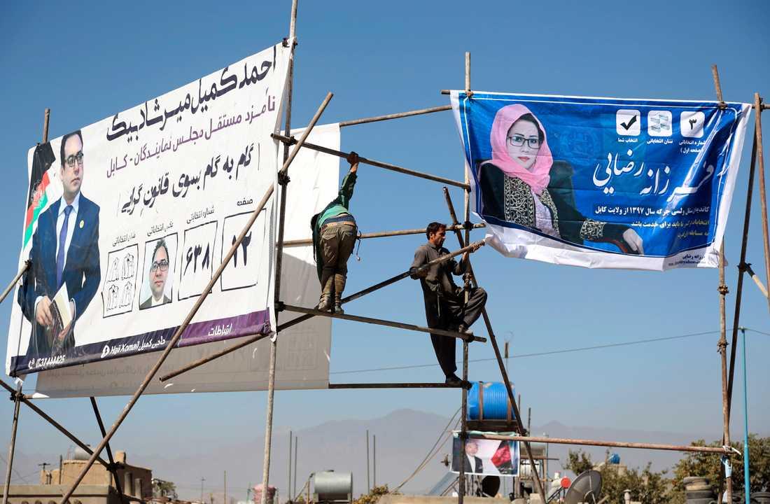 Valreklam sätts upp på en ställning i Kabul för kandidater till Afghanistans parlamentsval på lördag.