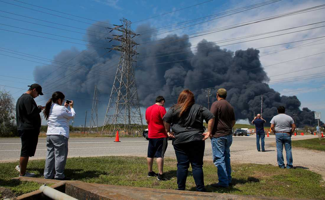 Personer i Houston, Texas samlas för att titta på rökmolnet som stiger från branden i ett företags lagringslokaler i staden.
