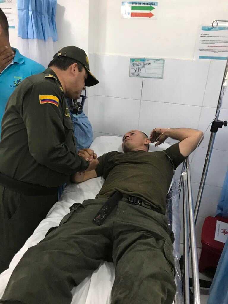 En skadad polisman får vård efter attacken.