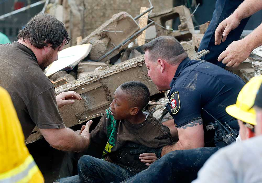 En pojke som fastnat under en rasad vägg vid Plaza Towers Elementary School räddas