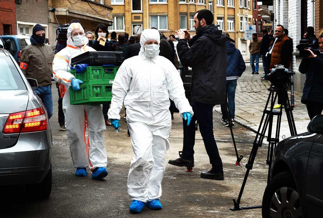 Polistekniker lastar ut föremål från en lägenhet i Anderlecht som kopplas till terrordåden en dag efter terrordåden.