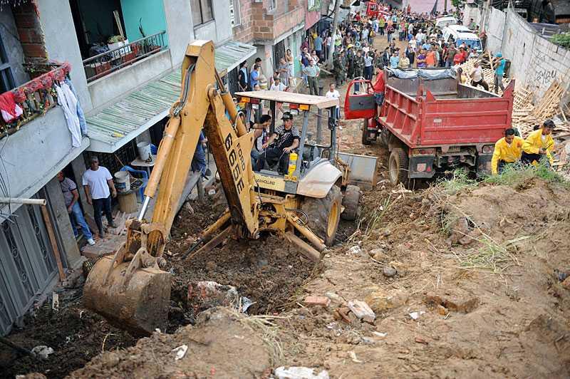 Flera hus begravdes under jordmassorna i La Gabriela. Oroliga anhöriga följer räddningsarbetet.
