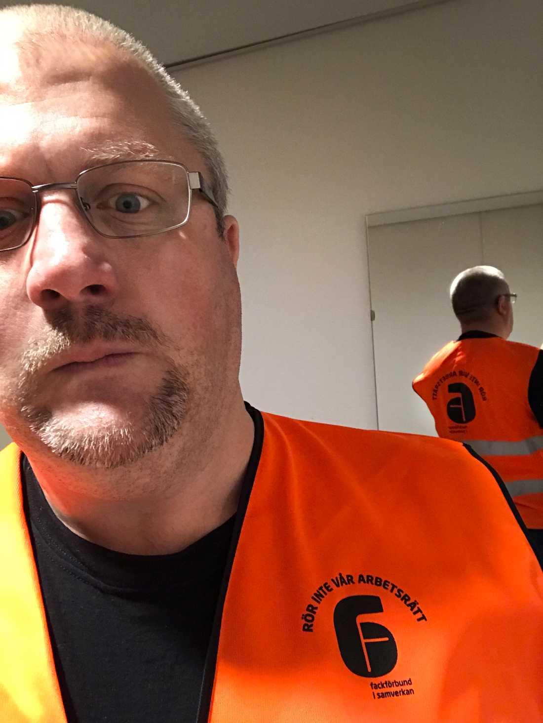 """Sven Höckert i den orangea västen märkt """"Rör inte vår arbetsrätt""""."""