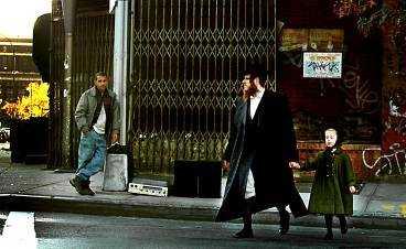 En ortodox jude och en flicka korsar en gata i Williamsburg, New York. I bakgrunden står en man och försöker sälja en stereo.