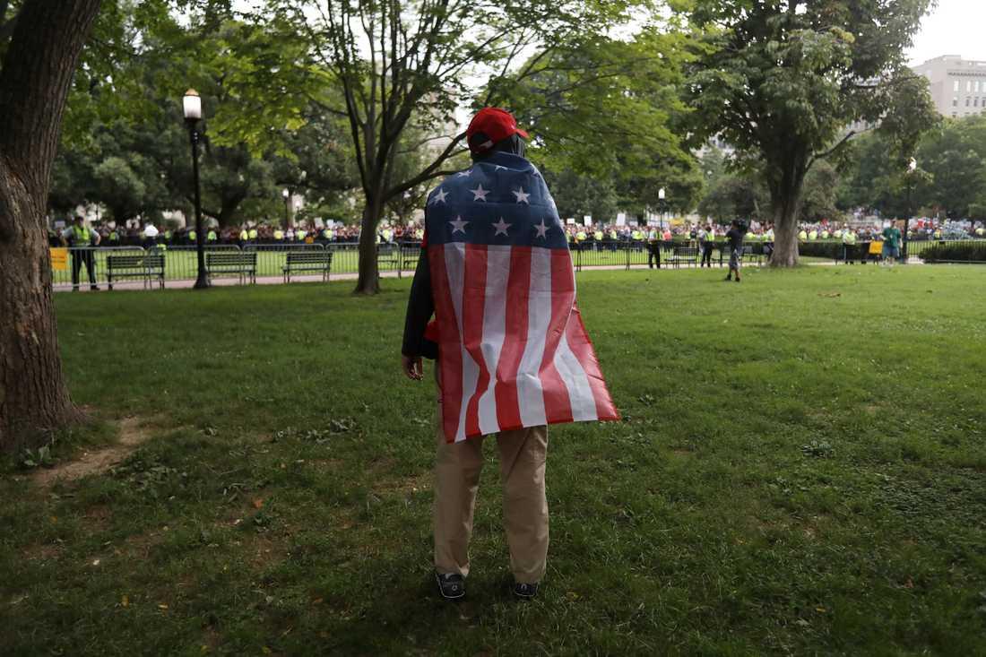 En demonstrant från Alt-right bär en amerikansk flagga vid demonstrationen i Washington.