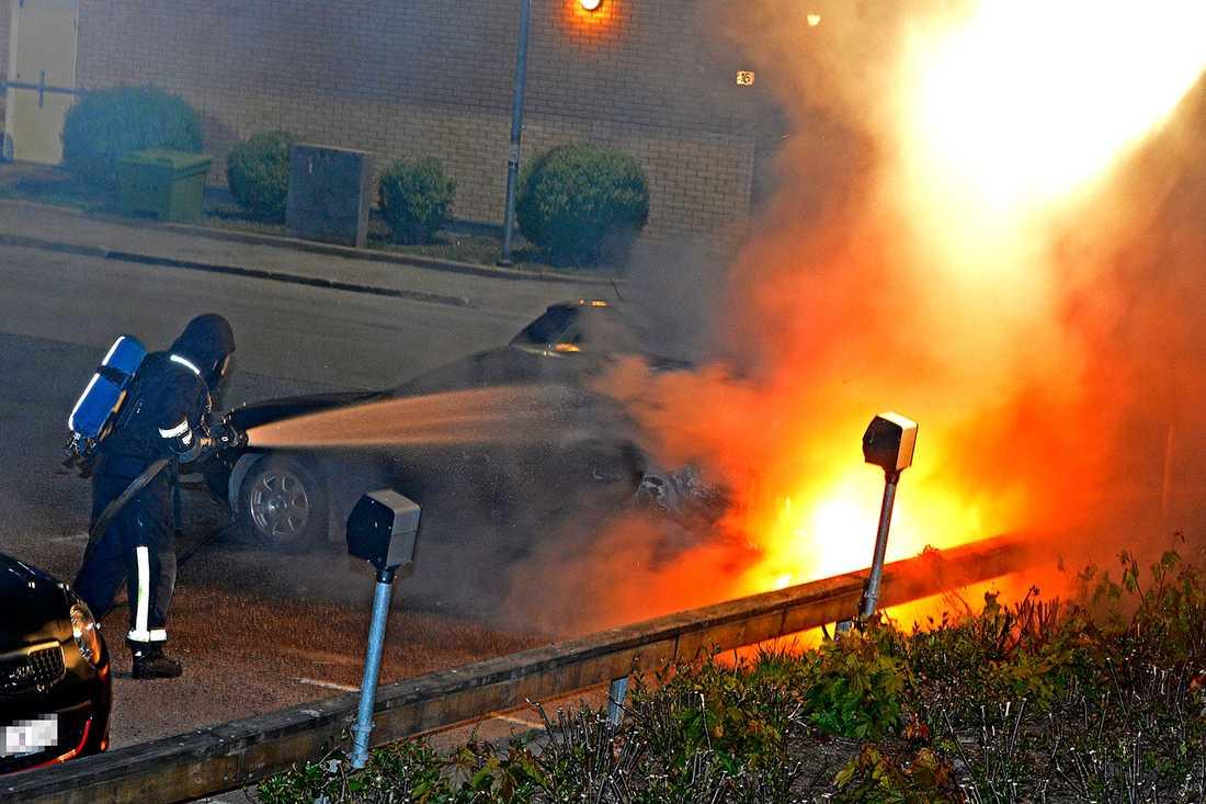 En brandman släcker en bilbrand i Hallunda.