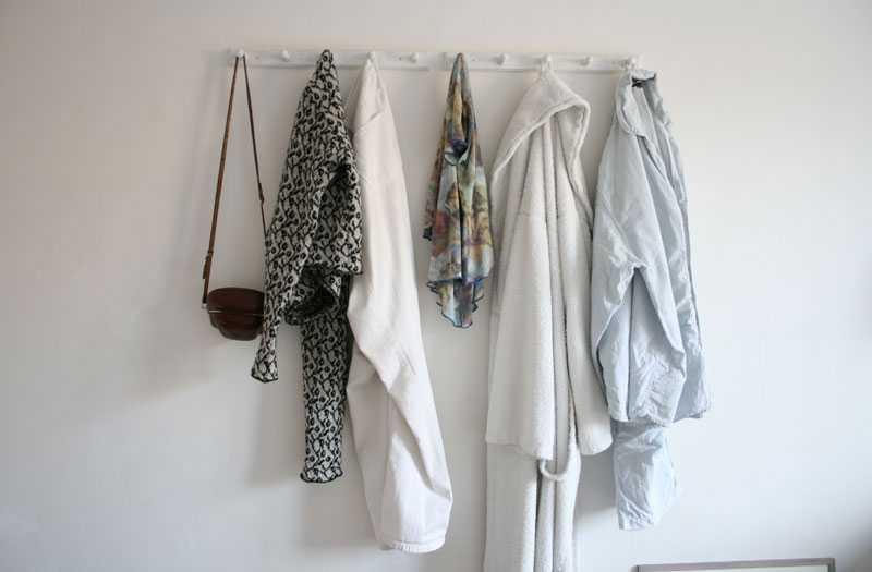 Som ett konstverk i sig blir den enkla klädhängaren i trä som utgör den enda dekorationen på väggen i sovrummet.