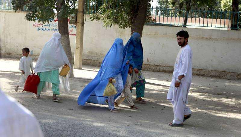Afghanska kvinnor med matkassar.