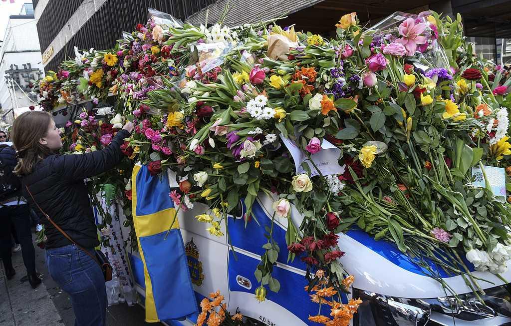 Blommor placeras på en polisbil utanför Åhlens (där lastbilen körde in i varuhuset) i samband med manifestationen för kärlek och omtanke på Sergels torg i Stockholm på söndagen efter terrorattacken på Drottninggatan. 4 personer omkom vid fredagens terrorattack.