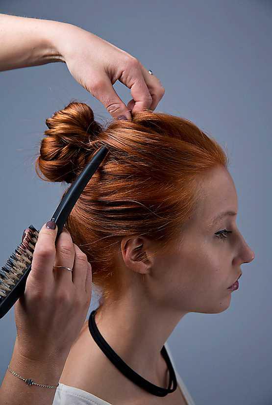 4. Trä ett dubbelt hårband över huvudet. Håll det på plats med ena handen i nacken samtidigt som du med andra handen drar det från pannan och en liten bit bakåt mot knuten. Det gör att fronten blir helt slät, medan du får volym på partiet närmast knuten.