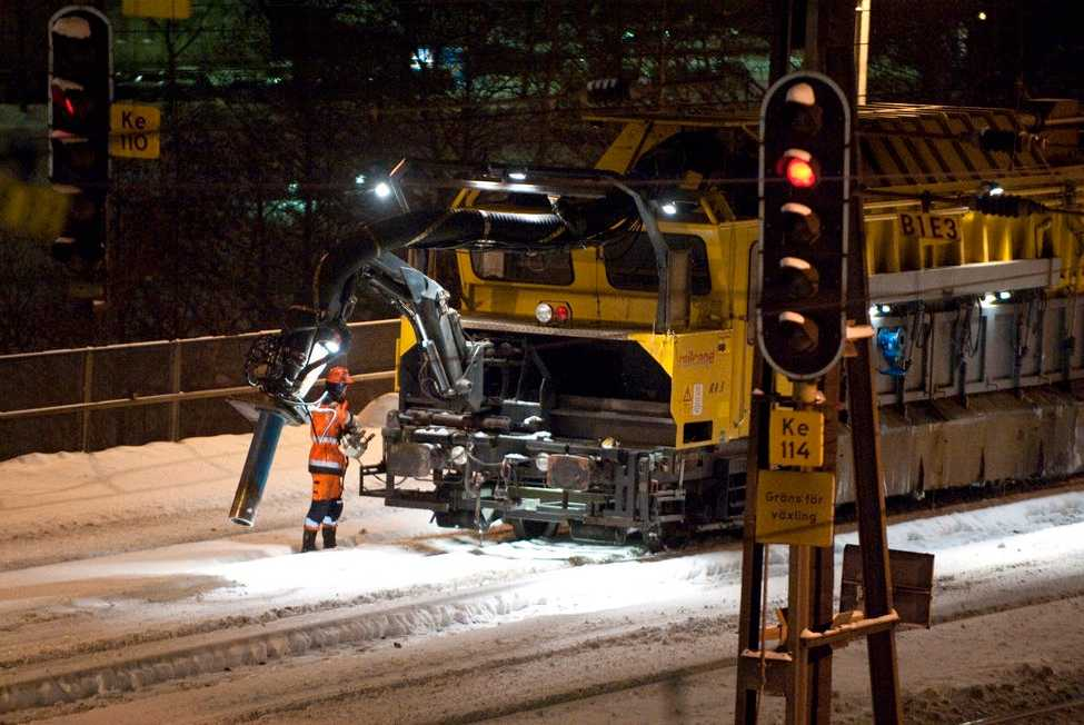 Banarbetare med snöröjningmaskin som blåser bort snö med högtrycksblås vid spåren mellan Stockholms Central och Karlbergs station sent på måndagskvällen.