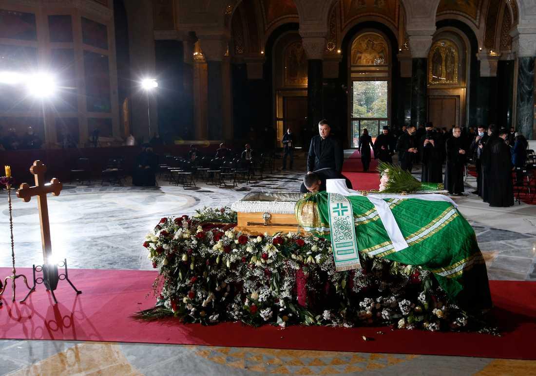 En man kysser plexiglaset över den serbiske patriarken Irinejs kistan på söndagen.