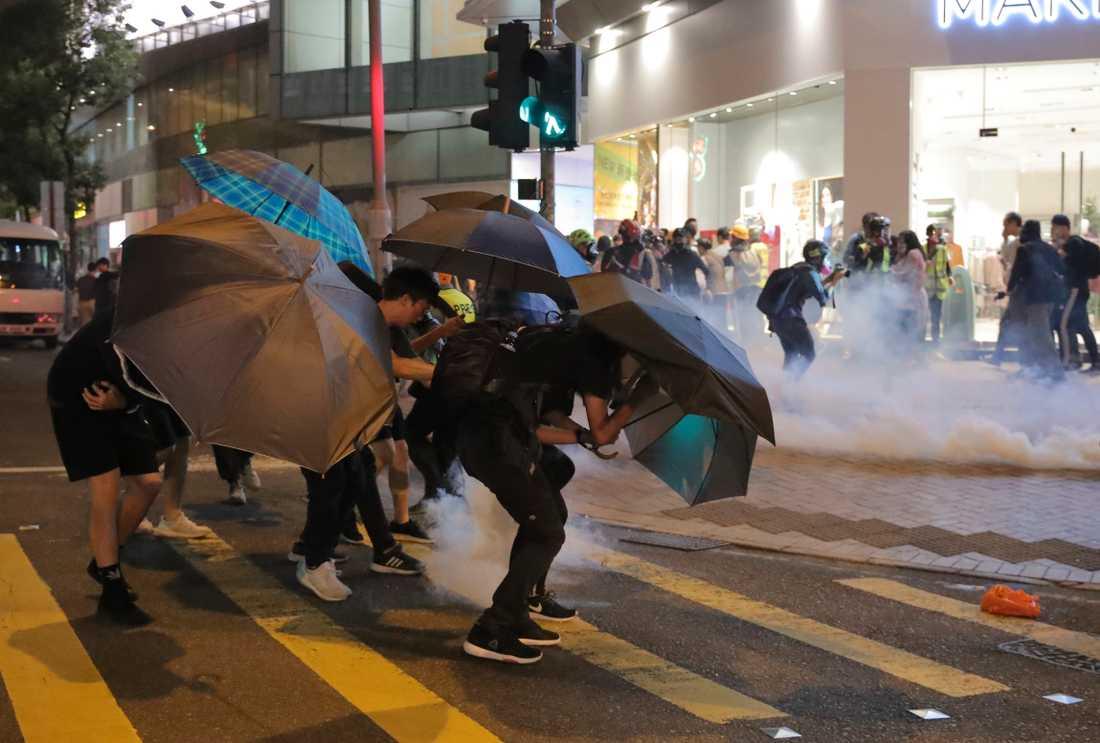 Aktivister skyddar sig mot tårgas med paraplyer.