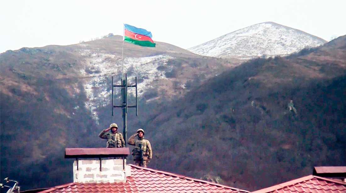 Azeriska soldater gör honnör sedan armén gått in i den övergivna staden Kalbajar, ett av de områden som Armenien lämnat över kontrollen av. Bilden kommer från azeriska försvarsdepartementet.