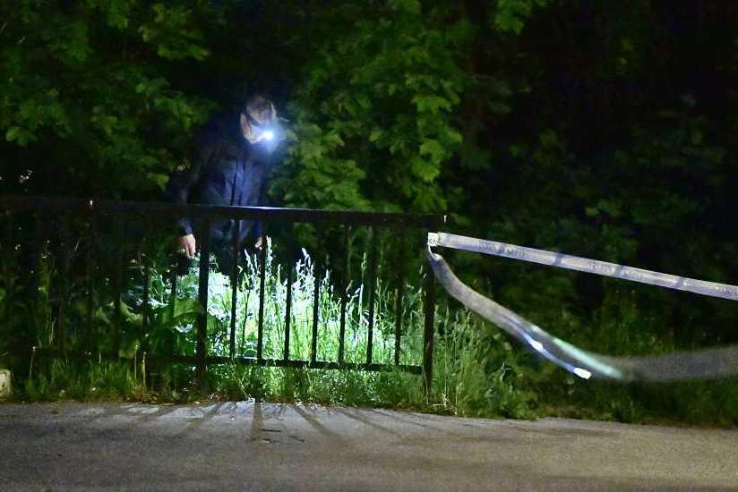 Polisen söker efter spår i buskarna utanför flerfamiljshuset.