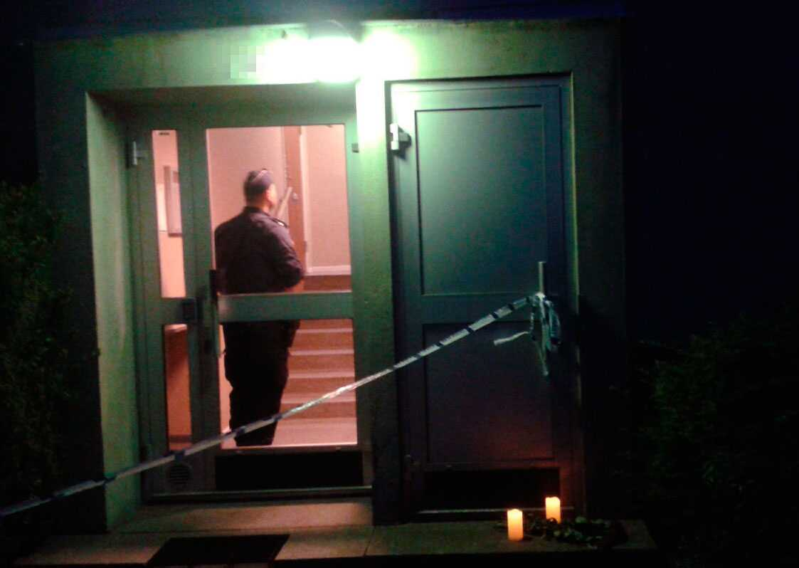 Polis i trapphuset. Ett par ljus och en blomma har lagts ner för att hedra den unga kvinnan.
