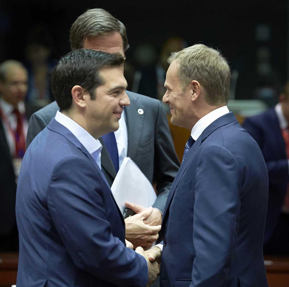 Tsipras och Tusk skakar hand under EU-toppmötet i Bryssel.
