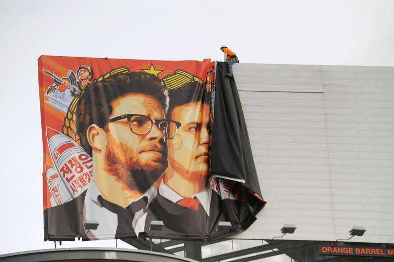 """MONTERAR NER MARKNADSFÖRINGEN En stor banderoll för filmen """"The interview"""" plockas ner i Hollywood efter att hoten om terrorattacker fått Sony att ställa in premiären."""