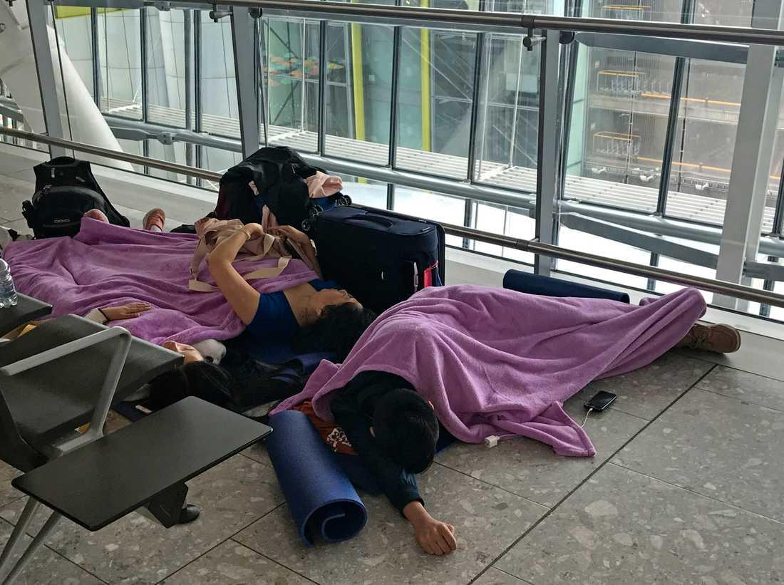 Resenärer som vilar på golvet på terminal 5 på flygplatsen Heathrow efter att ett oväder orsakat stora förseningar i flygtrafiken.
